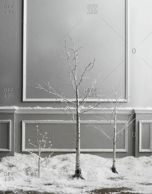 Birch trees in fake snow against wall