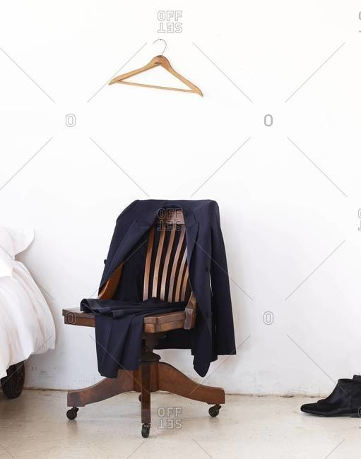Elegant suit hanging on wooden swivel chair standing in bedroom