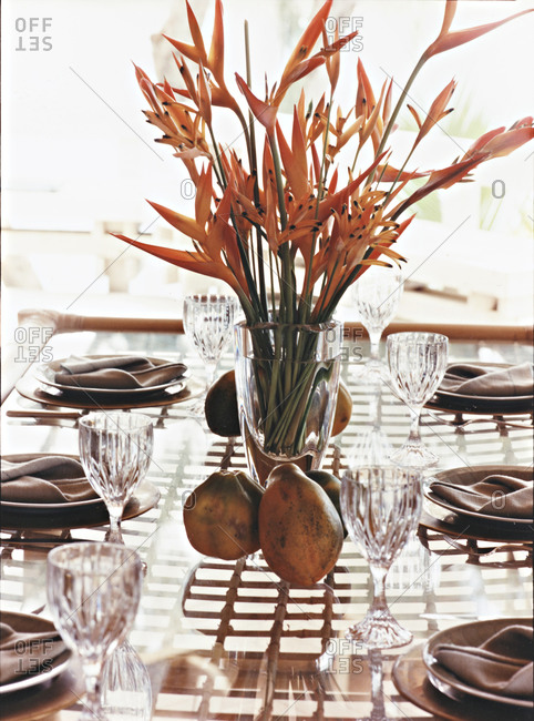 Still life of table setting with birds of paradise flowers and papayas as ornamentation