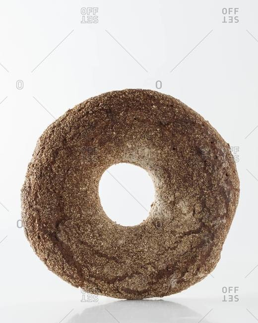 Whole-grain bagel on white background