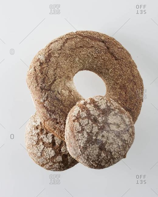 Whole-grain bagel and buns on white background