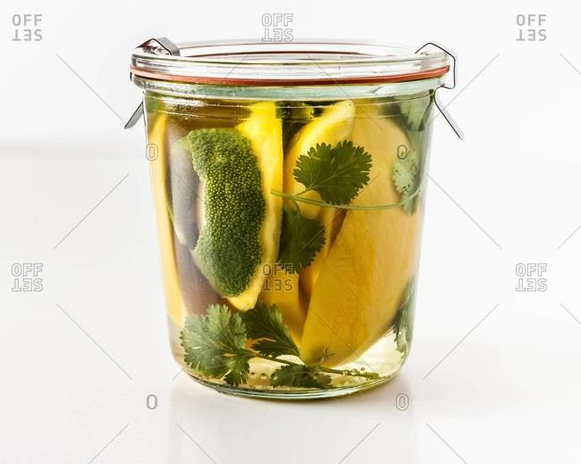 Jar of tequila with sliced mango, lime, and cilantro