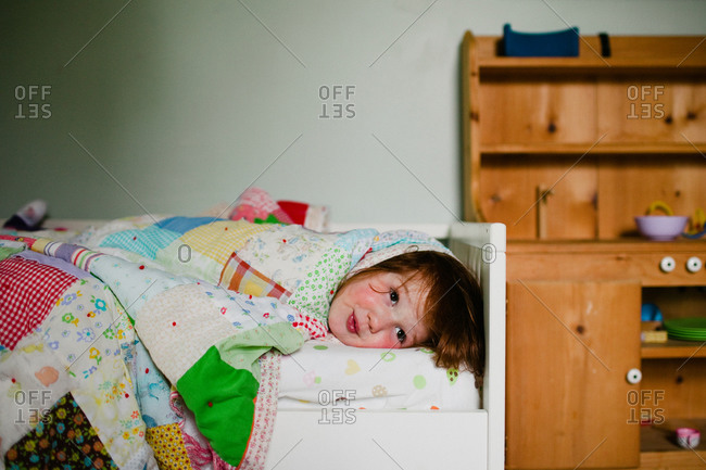 Redhead girl wrapped up in quilt