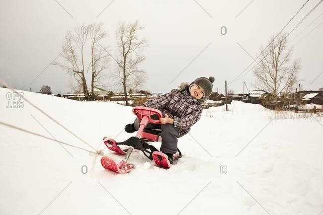 Asian girl riding sled in snow