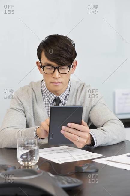 Korean businessman using digital tablet in office