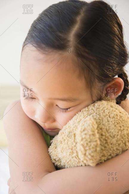 Korean girl hugging teddy bear