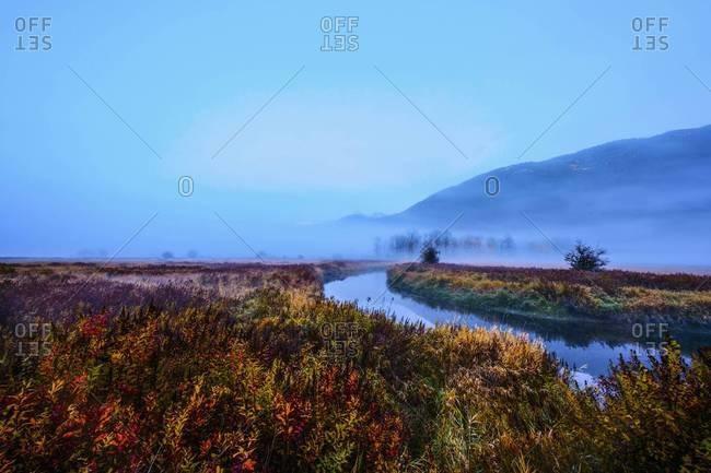 Fog over river and rural landscape