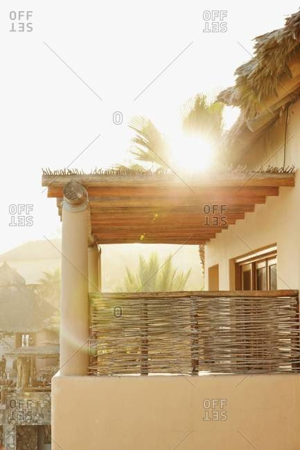 Sun shining over palm trees and resort balcony