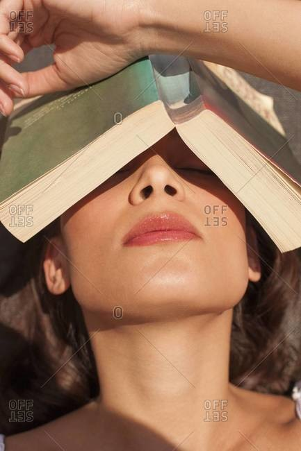 Woman sleeping with a book resting on her forehead