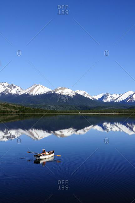 A woman rows a boat across a reflective lake