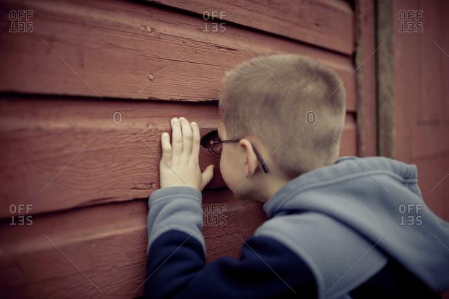 A young boy peeps through a wall