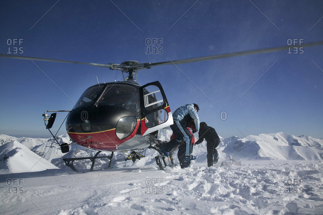 A helicopter lands with 4 off-piste skier at the top of a mountain, Limone in Italy