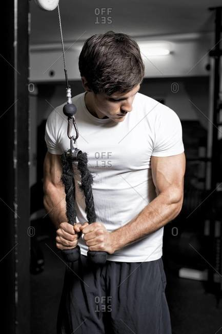 Man in fitness center doing cable workout