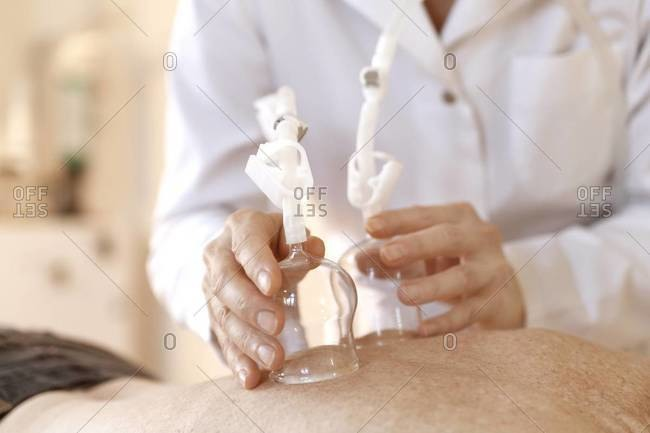 Female alternative practitioner treating senior woman with vacuum cupping therapy