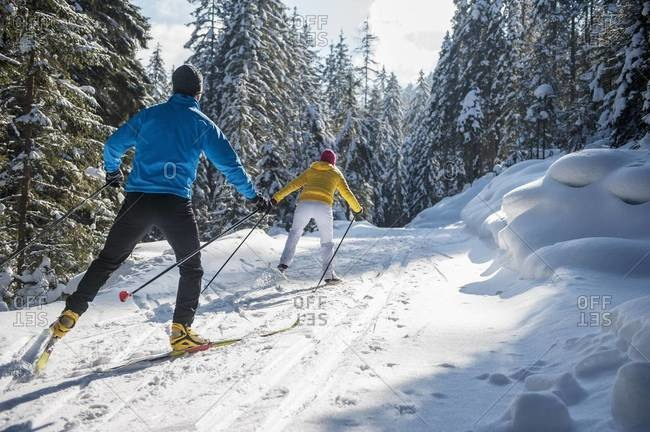 Rear view of couple cross-country skiing