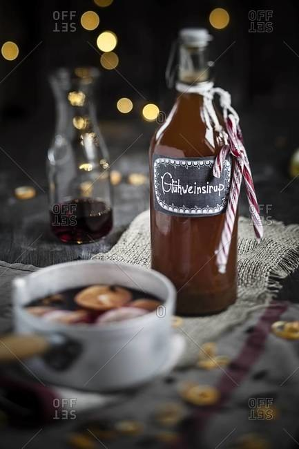Pot of mulled wine, slices of lemons and oranges and spices and a bottle with syrup