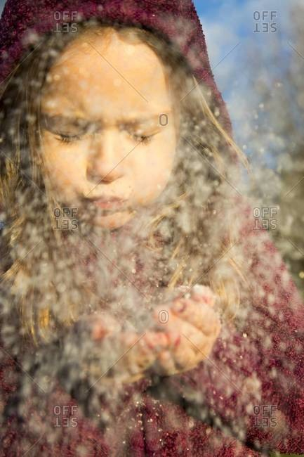 Portrait of girl blowing snow out of her hands