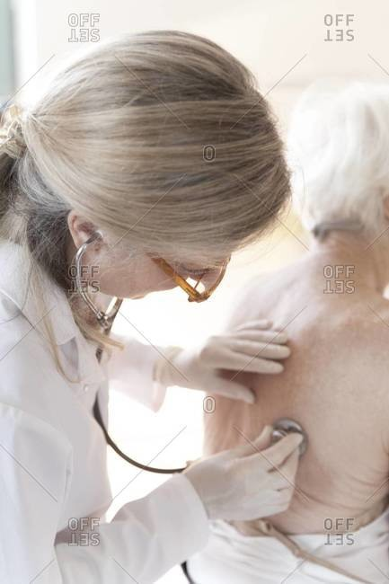 Doctor using a stethoscope on an older woman's back