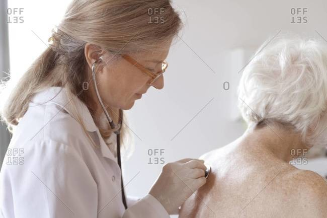 Doctor auscultating senior woman with stethoscope