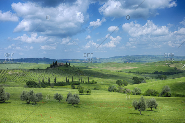 Val d'Orcia, Italy - October 16, 2010: Green rolling landscape with fluffy clouds