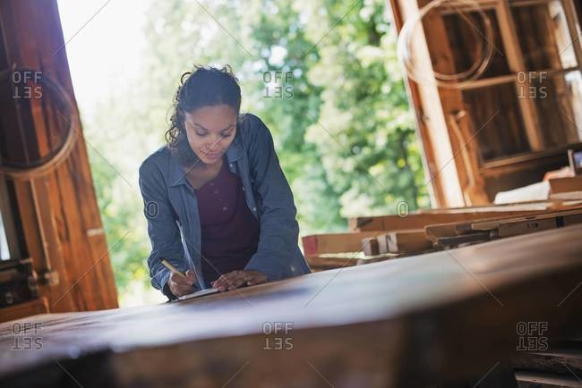 Woman working with reclaimed timber in a woodwork workshop.