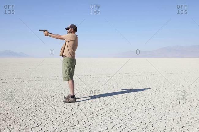 Man aiming hand gun, standing in vast, barren desert