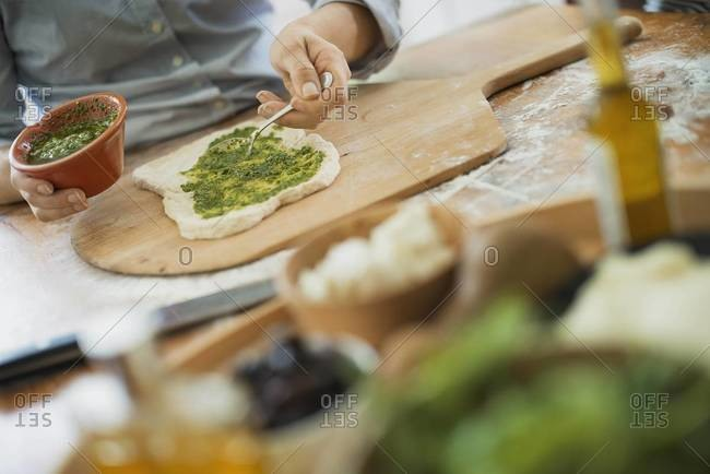 Person making a wrap with fresh ingredients and green salsa.