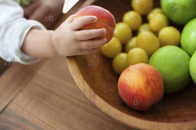 Toddler grasping peach from wooden bowl