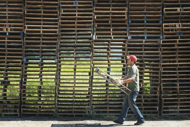 Man carrying wooden pallet in front of huge stack of objects