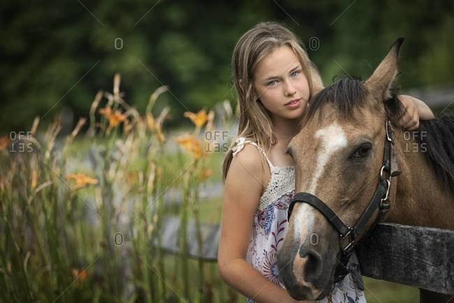 Young girl with a pony wearing halter, in a field full of wild flowers