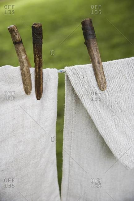 Close-up of old clothespins holding linen on the clothesline