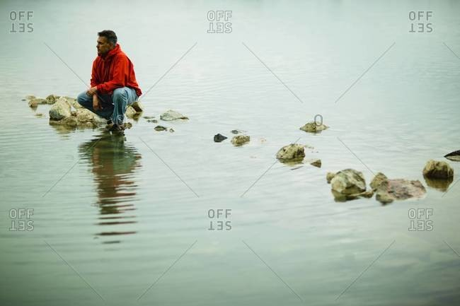 Man squatting on a stepping stone
