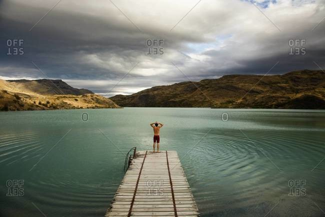 Young man standing at the end of a wooden pier in Torres del Paine National Park, Chile