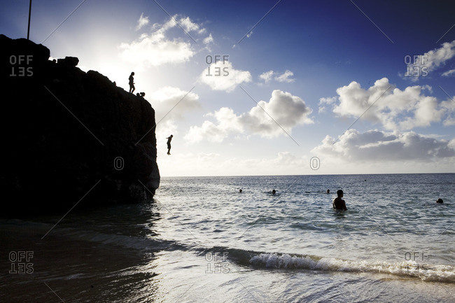 Silhouette of men jump off cliff into Pacific Ocean