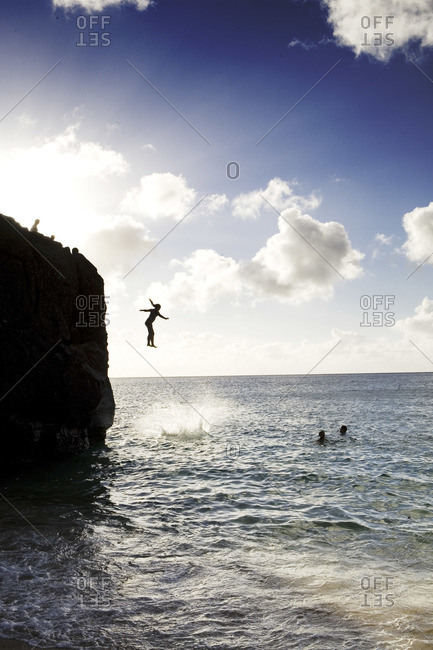 Silhouette of person jumps off cliff into Pacific Ocean