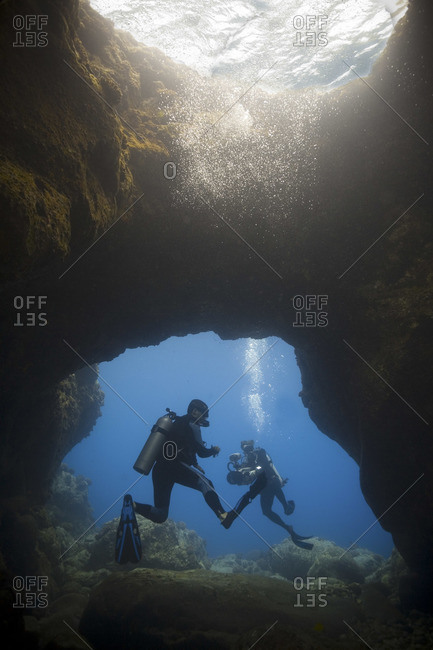 Divers in front of an underwater cave