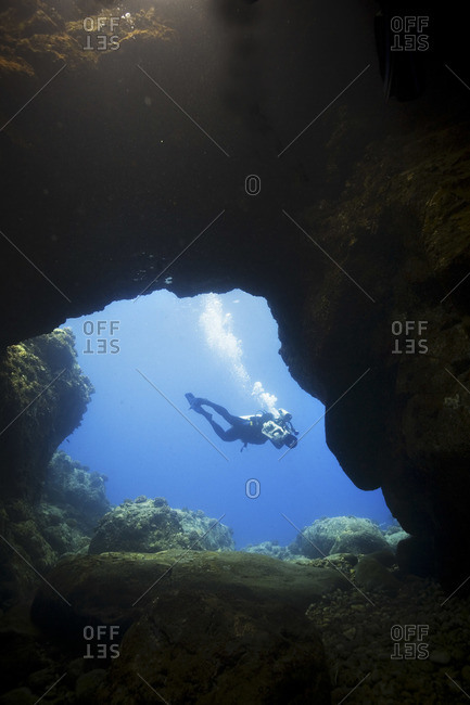 Diver in front of an underwater cave