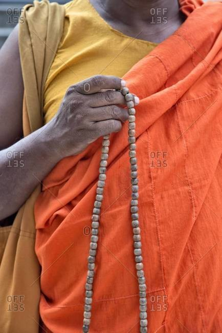 Detail of a Buddhist monk holding prayer beads. Mahabodhi Temple, Bodh Gaya, India