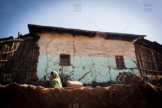 Low angle view of senior Ethiopian woman walking in village