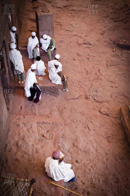 Ethiopian men talking and praying in front of church
