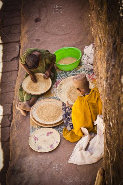High angle view of man and woman sorting grain