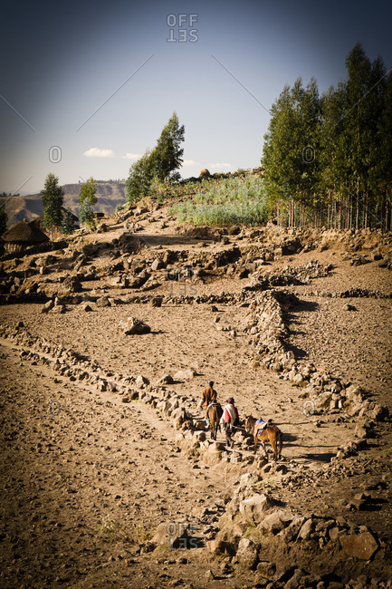 High angle view of local men walking with horse across rocky area