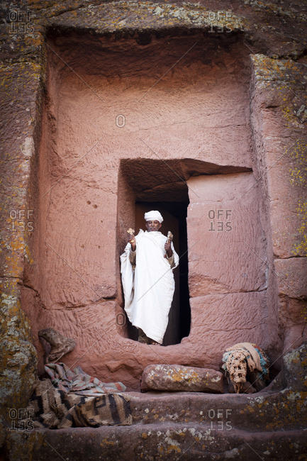 Ethiopian priest holding cross and walking out from ancient church