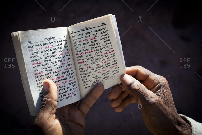 Close up of a man reading a monthly version an Amharaic Bible