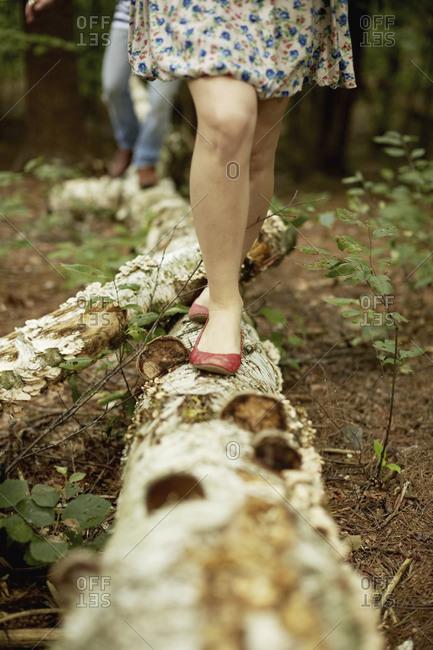 Woman walking along a fallen tree trunk in the woods.