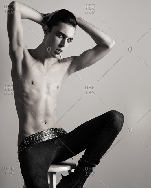 Androgynous male model sitting on a stool