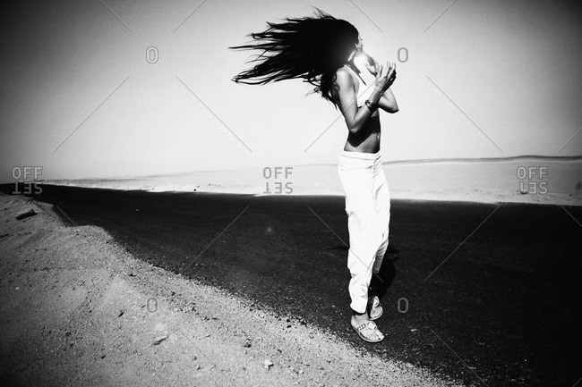 Woman standing on a desert road, in the blowing wind