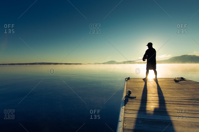 Rear view of man fishing at sunrise