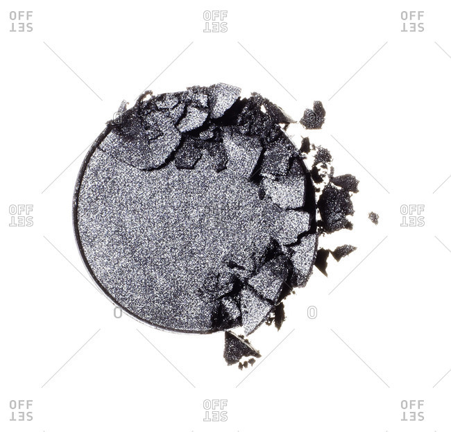Crushed, gray eye shadow smudged on white background