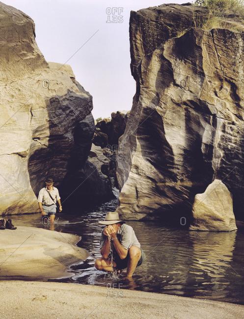 Men refreshing themselves while trekking through the African wilderness in Kenya